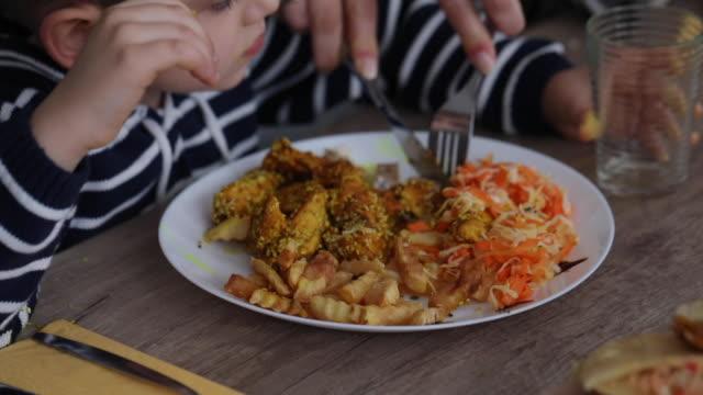 vidéos et rushes de repas de coupe de mère pour son fils mignon pendant le déjeuner de famille - expression positive