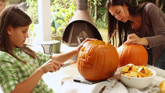 stockvideo's en b-roll-footage met ms zi mother cutting pumpkin with children / los angeles, california, united states - snijden