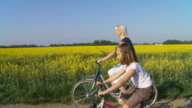hd steady shot: mother cycling with her daughter - young adult videos stock videos and b-roll footage