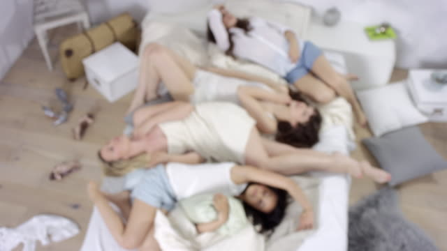 mother, daughter and two friends lying together in bed - coming into frame and jumping into bed / enjoying time together - reclining stock videos and b-roll footage