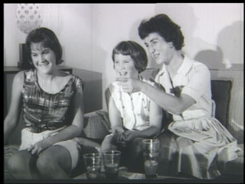 B/W 1961 mother + daughters sitting on couch watching television + laughing