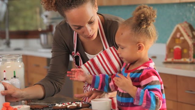 ms tu mother decorating gingerbread cookies with daughter (2-3) in kitchen / richmond, virginia, usa - sweet food stock videos and b-roll footage