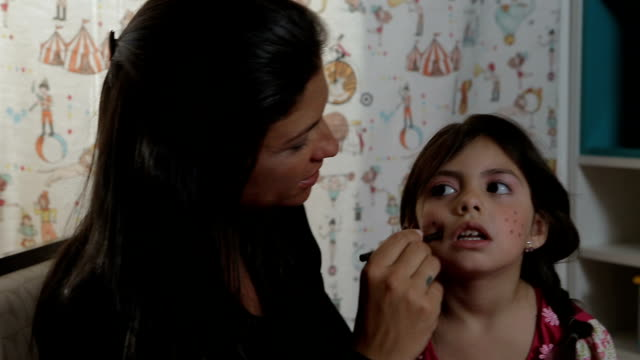 Mother Does Her Daughter's Make-up and They Smile to Each Other