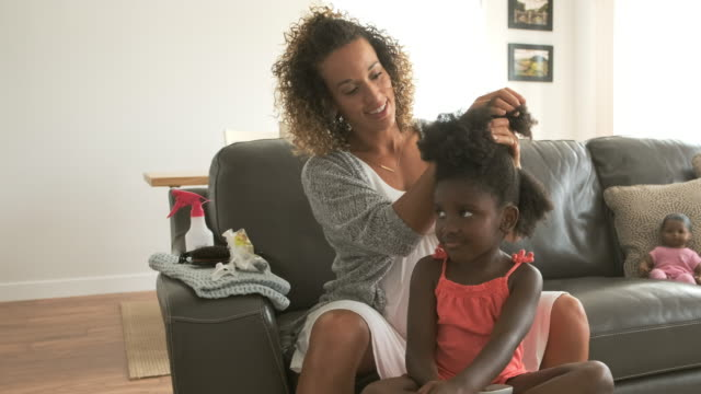 a mother doing daughter's hair - hairstyle stock videos and b-roll footage