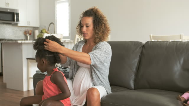 a mother doing daughter's hair - hairstyle stock videos & royalty-free footage