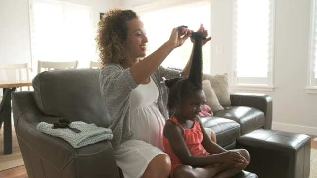 vídeos de stock e filmes b-roll de a mother doing daughter's hair - cabelo preto