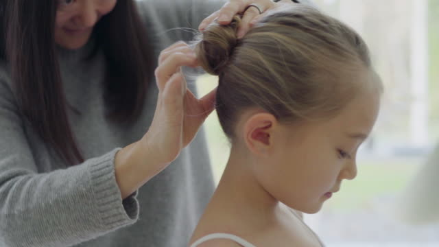 mother doing daughter's hair - hair bun stock videos & royalty-free footage