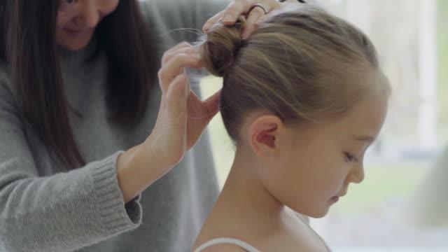 mother doing daughter's hair - chignon video stock e b–roll