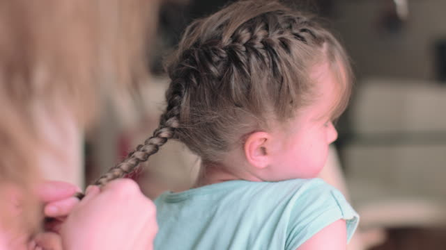 mother doing daughters hair - braided hair stock-videos und b-roll-filmmaterial