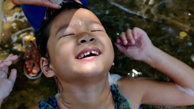 母は、彼女の娘のための安全で自然な方法から頭シラミ治療をしています - hair treatment点の映像素材/bロール