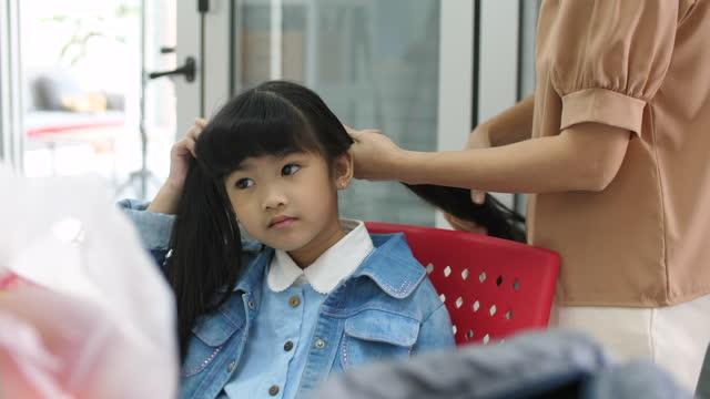 娘の髪をしている母親 - 髪をブラシでとく点の映像素材/bロール