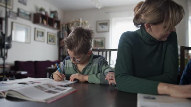 vídeos de stock, filmes e b-roll de mãe fazendo lição de casa com seus filhos - panning