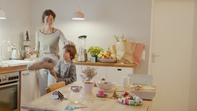 vidéos et rushes de mother doing house work with child playing with hobby horse - famille avec un enfant