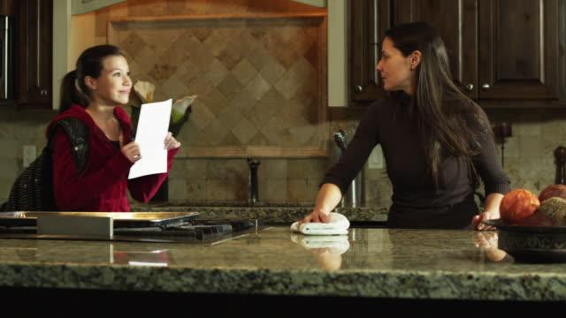 ms tu mother doing housework, daughter (9-10) showing exam results / orem, utah, usa - orem utah stock videos and b-roll footage