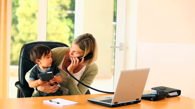 vídeos de stock, filmes e b-roll de mother doing office work with baby on her lap / cape town, western cape, south africa - telefone fixo