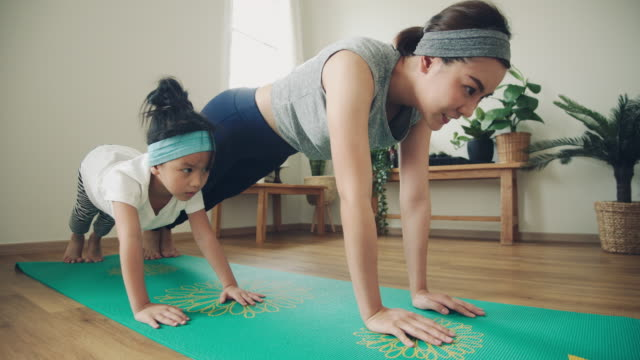 mother doing on yoga mat with little daughter at home. - zen like stock videos & royalty-free footage