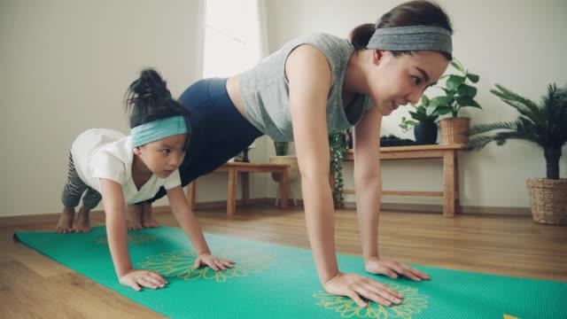 vídeos de stock, filmes e b-roll de mãe fazendo em tapete de ioga com a filhinha em casa. - família de duas gerações