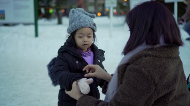 mother dressed up for her daughter in the snowy day - ethnicity stock videos & royalty-free footage