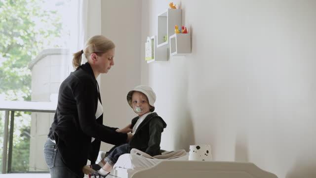 vídeos de stock, filmes e b-roll de ms mother dressing her baby / montreal, quebec, canada - bico