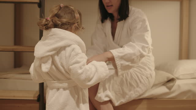mother dressing up baby girl in bathrobe in hotel room - bathrobe stock videos & royalty-free footage