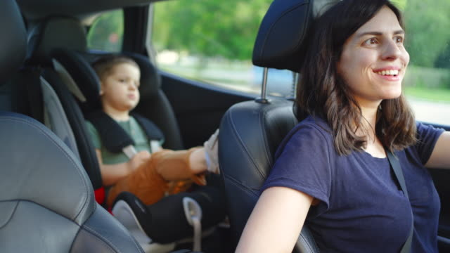 mother driving a car while her son is sitting in a car safety seat - family with one child stock videos & royalty-free footage