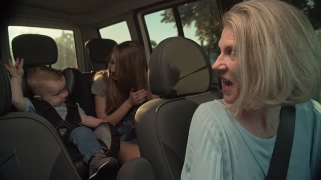 vídeos y material grabado en eventos de stock de madre conduciendo coche con niños - asiento de atrás