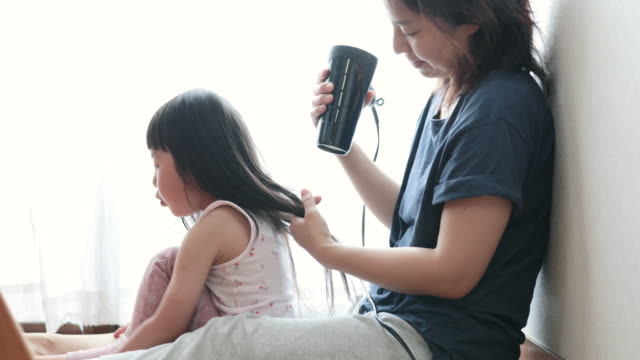 mother drying her daughter's hair with dryer - one parent stock videos & royalty-free footage
