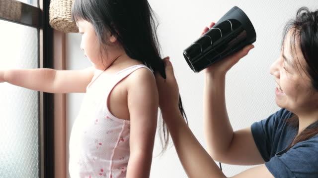 娘の髪を乾燥機で乾かす母 - 電化製品点の映像素材/bロール