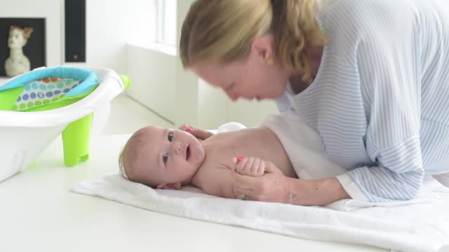 vídeos de stock e filmes b-roll de mother drying off newborn baby after bath. - banheira