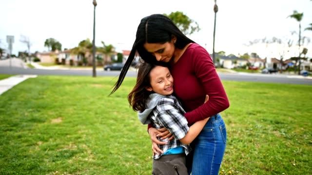 vidéos et rushes de mère embrasser le fils dans un parc public - latin american culture