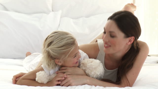 ms mother embracing daughter (8-9) lying on front on bed / cape town, western cape, south africa - lying on front stock videos & royalty-free footage