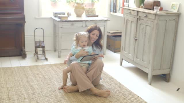 vidéos et rushes de mother entertaining daughter with digital tablet. - assis en tailleur