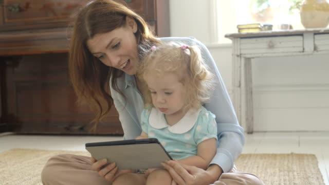 vídeos de stock e filmes b-roll de mother entertaining daughter with digital tablet. - colo