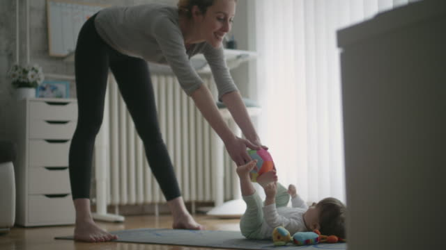 4k: mother exercise with her baby at home. - exercise room stock videos & royalty-free footage