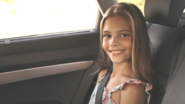 vidéos et rushes de mère de fixation ceinture pour jeune fille dans la voiture - journey