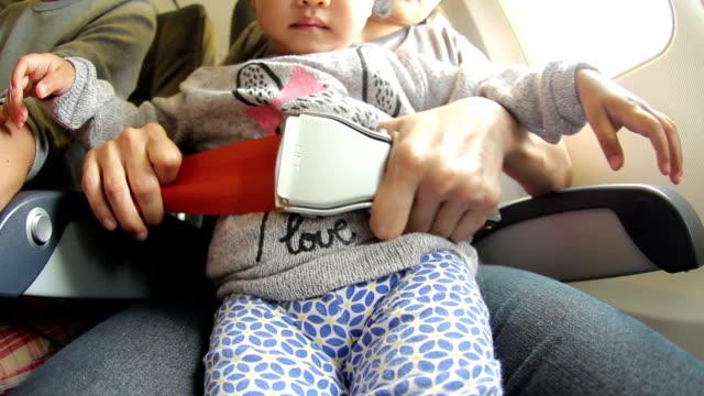 hd: mutter befestigen gurt für die tochter auf flugzeug - sicherheitsgurt sicherheitsausrüstung stock-videos und b-roll-filmmaterial