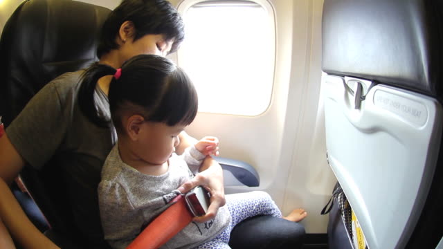 HD : Mother Fastening Seatbelt for daughter on Airplane