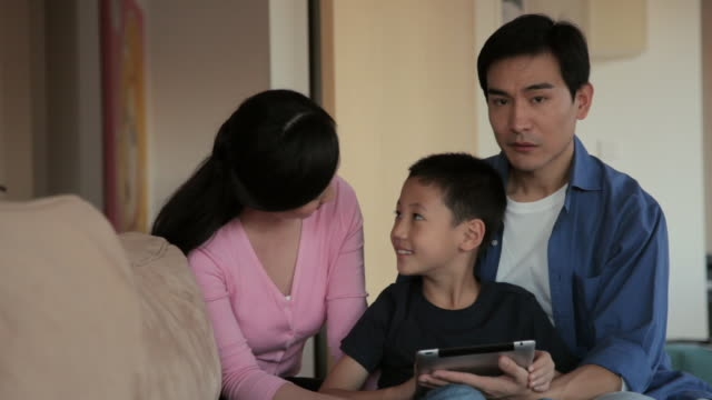 ms mother, father and son using digital tablet in living room / china - 6 7 jahre stock-videos und b-roll-filmmaterial