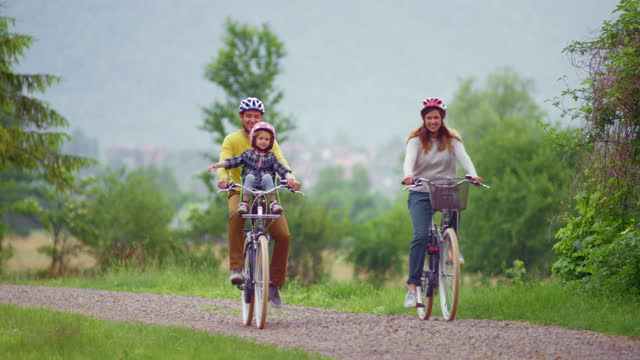 mother, father and their small daughter riding bicycles in the countryside - bicycle seat stock videos & royalty-free footage
