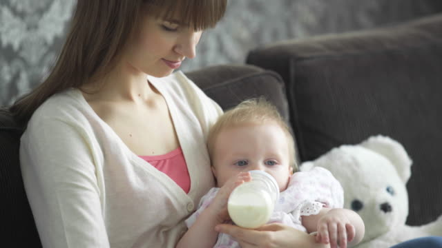 stockvideo's en b-roll-footage met cu mother feeding a baby a bottle of milk - voeren