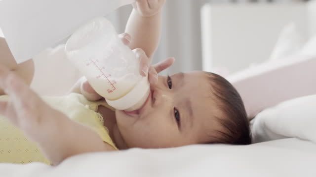 mother feeding asian newborn girl with milk from a bottle on bed at home - baby milk stock videos & royalty-free footage