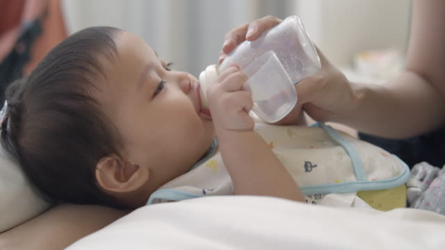 Mother feeding asian newborn girl with milk from a bottle
