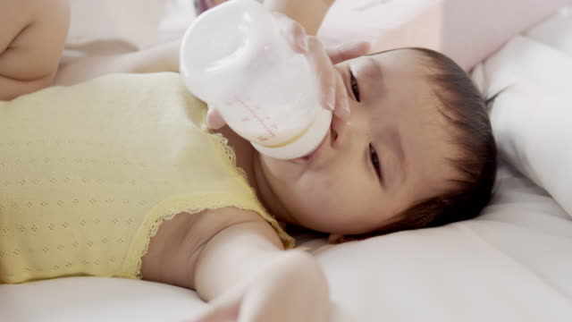 mother feeding asian newborn girl with milk from a bottle - baby bottle stock videos & royalty-free footage