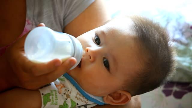 vídeos y material grabado en eventos de stock de mother feeding baby boy una botella - símbolo de arroba