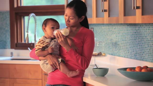 vídeos de stock, filmes e b-roll de ms tu mother feeding baby boy (6-11 months) from bottle / richmond, virginia, usa. - mamadeira