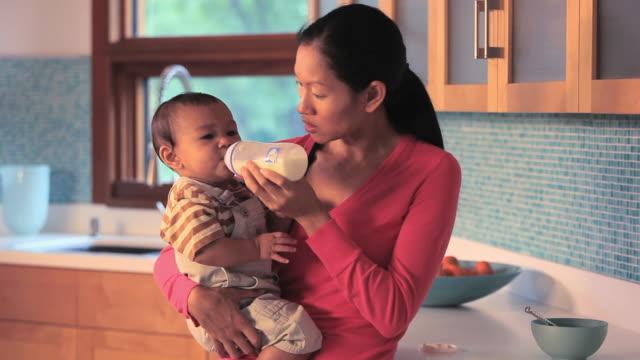 ms mother feeding baby boy (6-11 months) from bottle / richmond, virginia, usa. - 断る点の映像素材/bロール