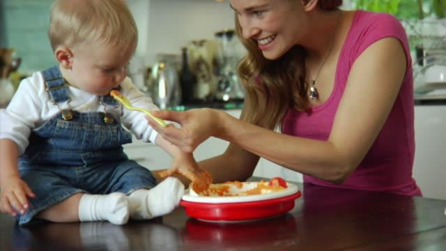 vídeos de stock, filmes e b-roll de slo mo ms mother feeding baby boy (6-11 months) / london, united kingdom - comida de bebê