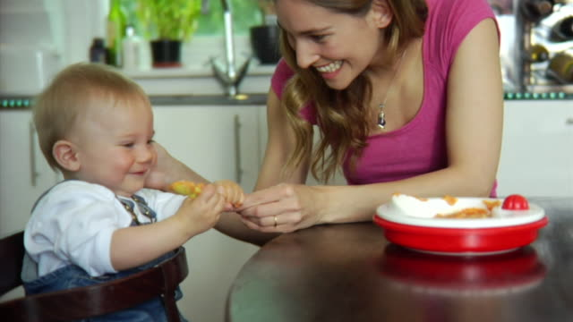 slo mo ms mother feeding baby boy (6-11 months) / london, united kingdom - bib overalls stock videos and b-roll footage