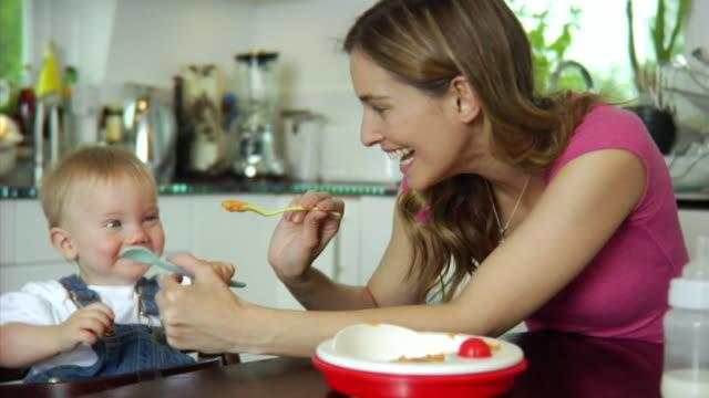 vídeos de stock, filmes e b-roll de slo mo ms mother feeding baby boy (6-11 months) / london, united kingdom - alimentando
