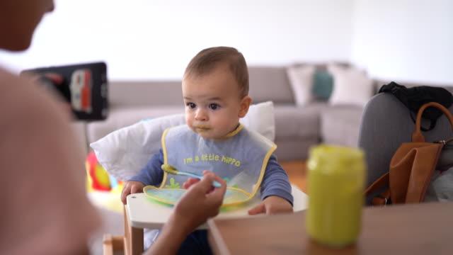vídeos de stock, filmes e b-roll de menino de alimentação da matriz que está sentando-se na cadeira elevada - comida de bebê